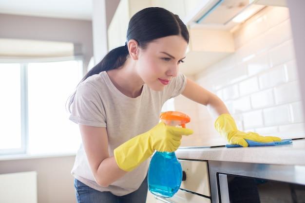 Geconcentreerde vrouw staat voor het fornuis en kijk ernaar. ze maakt het oppervlak schoon. meisje doet dat voorzichtig. ze draagt gele handschoenen.