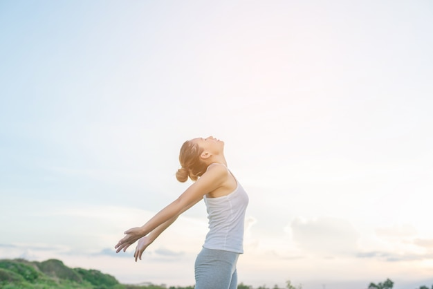 Geconcentreerde vrouw stretching haar armen met de hemel achtergrond