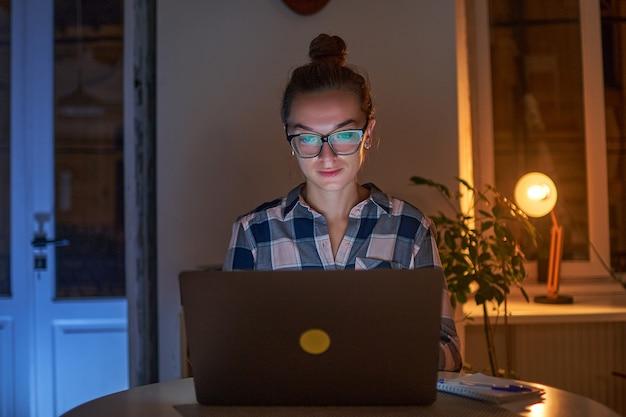 Geconcentreerde vrouw workaholic in glazen werkt 's avonds online op een laptop thuis