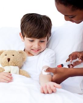 Geconcentreerde vrouwelijke arts die een kind een injectie geeft