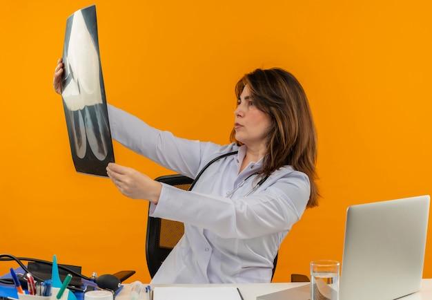 Geconcentreerde vrouwelijke arts van middelbare leeftijd die medische mantel en stethoscoop draagt ?? die aan bureau zit met het klembord van medische hulpmiddelen en laptop houdt en kijkt naar röntgenfoto geïsoleerd