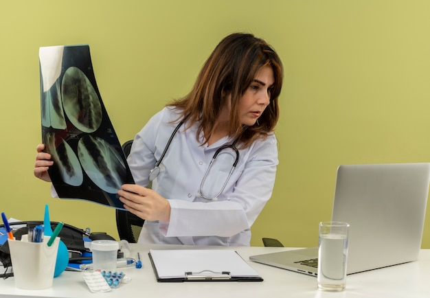 Geconcentreerde vrouwelijke arts van middelbare leeftijd die medische mantel en stethoscoop draagt ?? die aan bureau zit met medische hulpmiddelen die x-ray schot houden die laptop geïsoleerd bekijken