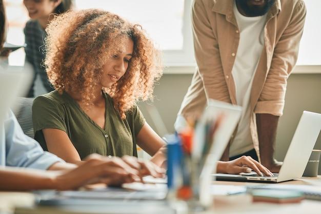 Geconcentreerde vrouwelijke kantoormedewerker die voor laptop zit