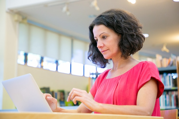 Geconcentreerde vrouwelijke klant die aan computer werkt