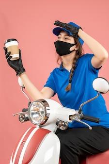 Geconcentreerde vrouwelijke koerier met een zwart medisch masker en handschoenen die bestellingen afleveren op perzikachtergrond
