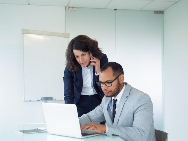 Geconcentreerde vrouwelijke manager die aan cliënt spreekt
