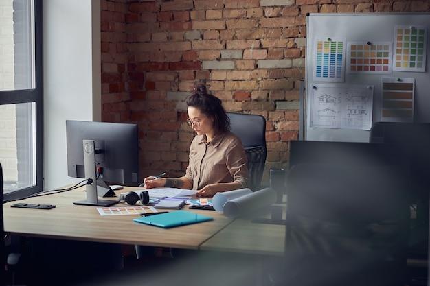Geconcentreerde vrouwelijke professionele ontwerper die door papieren kijkt terwijl hij aan een nieuw interieur werkt