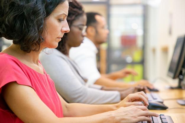 Geconcentreerde vrouwelijke student van middelbare leeftijd die in computerklasse studeert
