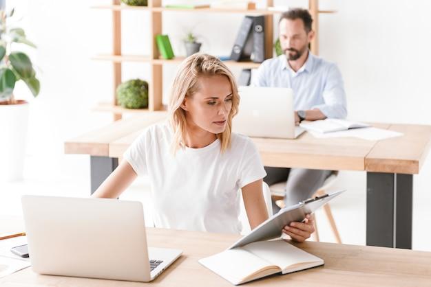 Geconcentreerde vrouwenmanager die aan laptop computer werkt