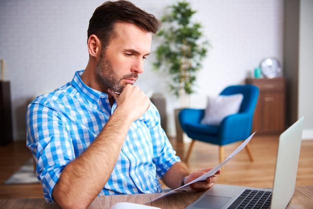 Geconcentreerde zakenman die belangrijke documenten aan zijn bureau leest