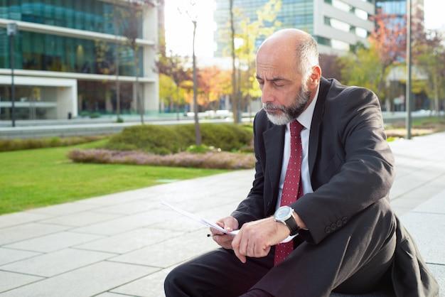 Geconcentreerde zakenman die documenten bekijkt