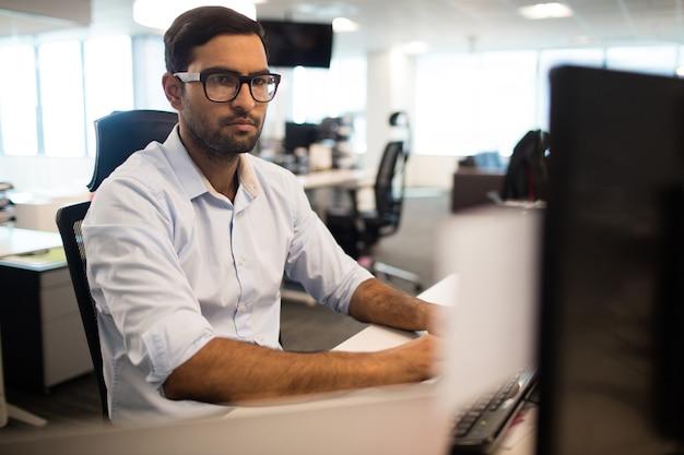Geconcentreerde zakenman die in bureau werkt