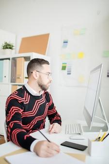 Geconcentreerde zakenman die nota maakt terwijl online analys houdt