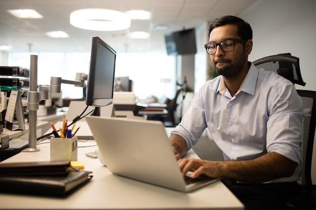 Geconcentreerde zakenman die op laptop in bureau werkt