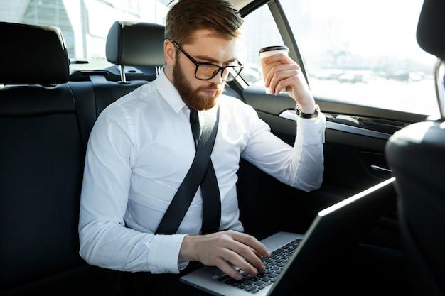 Geconcentreerde zakenman met behulp van laptop en kopje koffie te houden Premium Foto