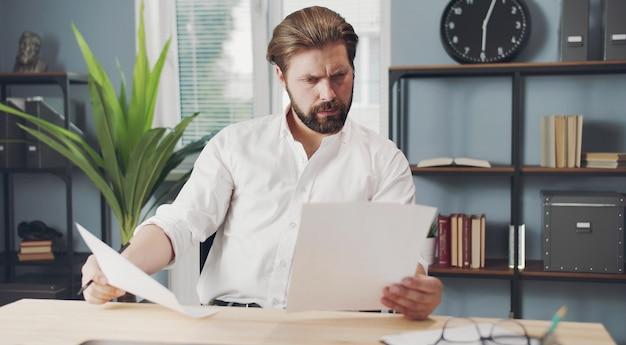 Geconcentreerde zakenman zittend aan een bureau met papieren in beide handen documenten te lezen