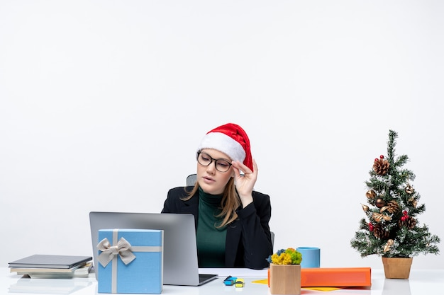 Geconcentreerde zakenvrouw met een kerstman hoed zittend aan een tafel met een kerstboom en een cadeau erop en haar mails controleren op witte achtergrond