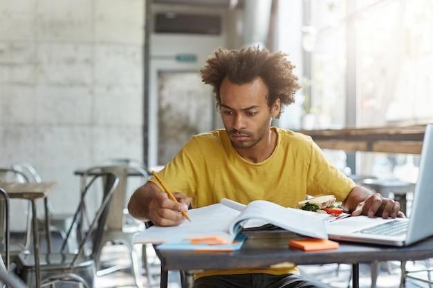 Geconcentreerde zwarte europese mannelijke student met baard voorbereiding voor onderzoekstest, zittend aan de universiteitskantine, sandwich eten, zoeken naar informatie op internet, met behulp van laptop