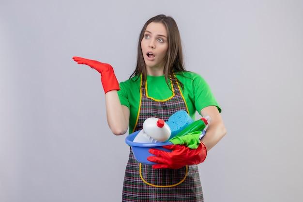Geconcereerde schoonmakende jonge vrouw die eenvormig in rode handschoenen draagt die schoonmakende hulpmiddelen houdt opgeheven hand op geïsoleerde witte muur