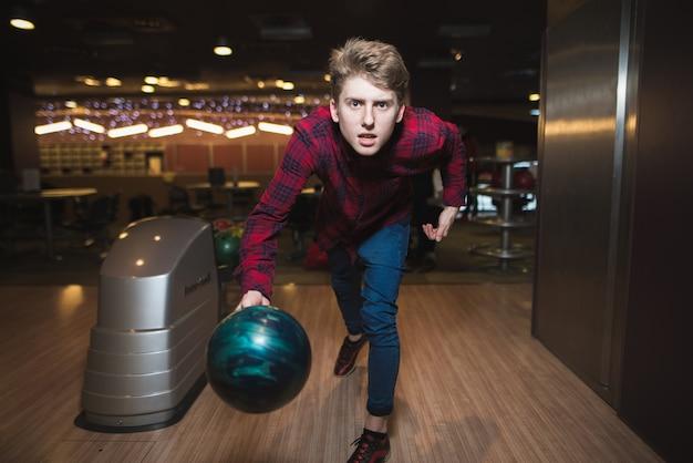 Gecondenseerde jonge man maakt een bowlingstaking. student staat op het punt een bal te gooien om te bowlen.