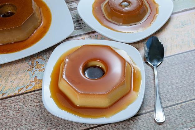 Gecondenseerde melkpudding met karamelsiroop, omringd door andere puddingen en een lepel. traditioneel braziliaans snoepje.
