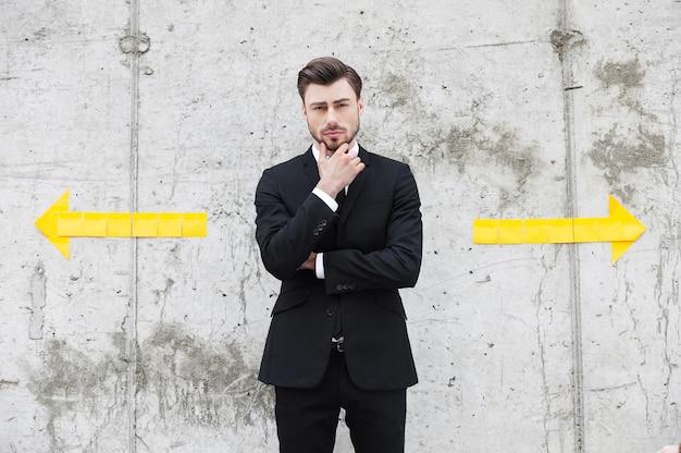 Geconfronteerd met de keuze. nadenkende jonge man in formele kleding die de hand op de kin houdt terwijl hij buiten staat