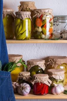 Geconserveerd en gefermenteerd voedsel. assortiment zelfgemaakte potten met diverse ingemaakte en gemarineerde groenten op een plank in de berging. huishouden, huishoudkunde, oogstbehoud