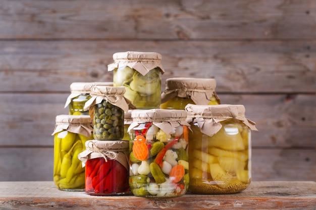 Geconserveerd en gefermenteerd voedsel. assortiment zelfgemaakte potten met verschillende ingemaakte en gemarineerde groenten op een houten tafel. huishouden, huishoudkunde, oogstbehoud