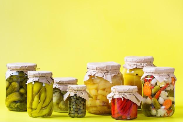 Geconserveerd en gefermenteerd voedsel. assortiment zelfgemaakte potten met verschillende ingemaakte en gemarineerde groenten op een tafel. huishouden, huishoudkunde, oogstbehoud