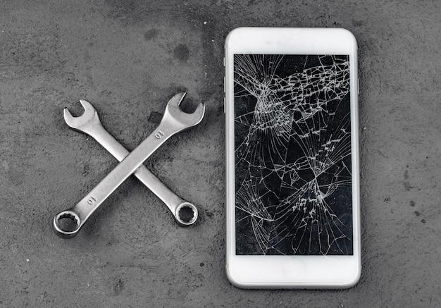Gecrashte smartphone met reparatiehulpmiddelen op grijze achtergrond