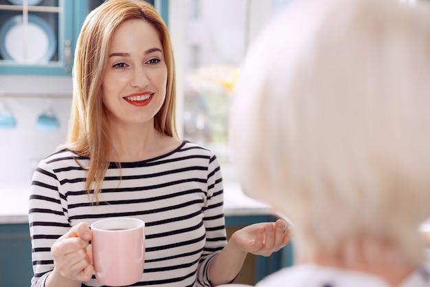 Gedachten delen. de focus ligt op een mooie jonge vrouw die met haar bejaarde moeder praat en liefdevol naar haar glimlacht terwijl ze over haar dag vertelt en koffie drinkt