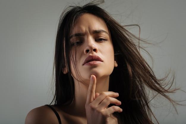 Gedachten. mooie meditatieve donkerharige jonge vrouw denken en staren en haar kin aan te raken