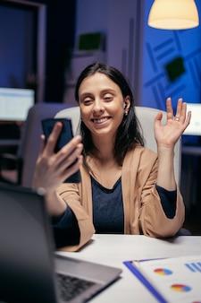 Gedag zeggen tijdens een teleconferentie met ondernemers die overuren maken. vrouw die aan financiën werkt tijdens een videoconferentie met collega's 's nachts op kantoor.