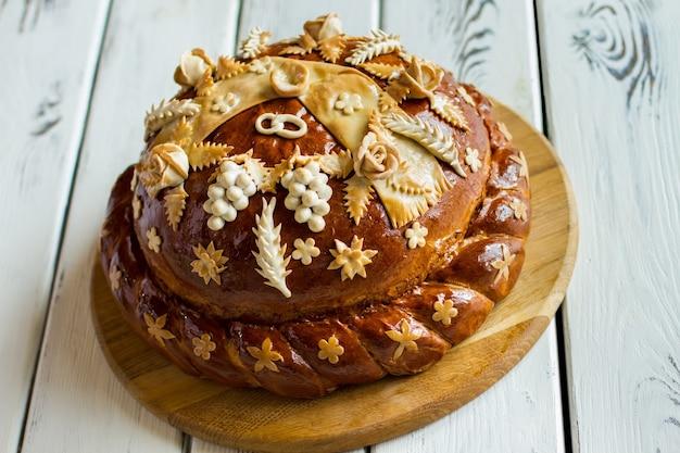 Gedecoreerd brood op een houten bord. gebakken brood van bruine kleur. met vriendelijke groeten aan de pasgetrouwden. leef in liefde en geluk.
