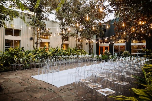 Gedecoreerde ceremoniële ruimte buiten met moderne transparante stoelen en prachtige slinger met veel bomen en planten
