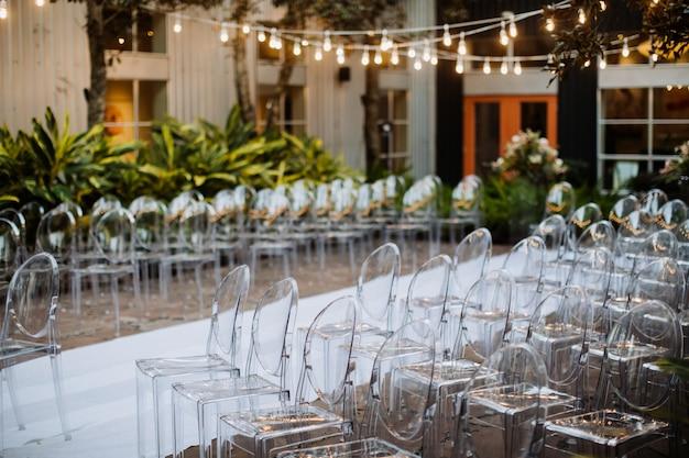 Gedecoreerde ceremoniële ruimte buiten met moderne transparante stoelen en prachtige slinger