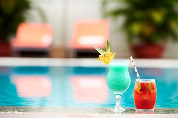 Gedecoreerde glazen van zoete heerlijke tourquoise en cocktails met rood fruit aan de rand van het zwembad