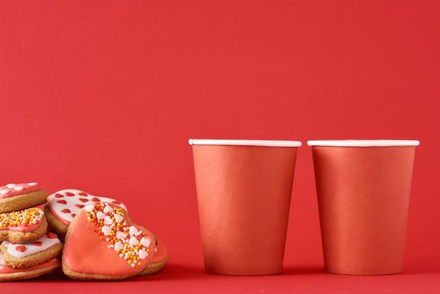 Gedecoreerde hartvormige koekjes en twee papieren koffiekopjes op rood oppervlak. valentijnsdag voedsel concept