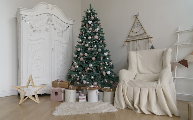 Gedecoreerde kamer voor kerstvakantie - geschenken onder kerstboom en witte kledingkast en overdekte fauteuil