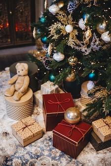 Gedecoreerde kerstboom met ballen en veel geschenken onder dennenboom