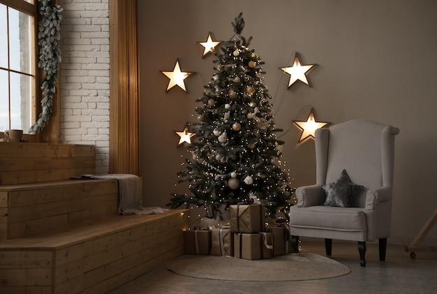 Gedecoreerde kerstboom met cadeautjes en grijze fauteuil met opgehangen sterren
