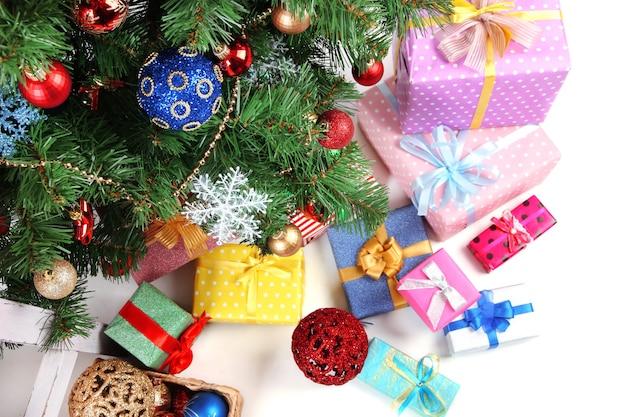 Gedecoreerde kerstboom met geschenken, close-up, geïsoleerd op wit