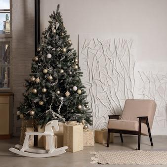 Gedecoreerde kerstboom met geschenken en hobbelpaard naast fauteuil