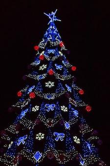 Gedecoreerde kerstboom met veelkleurige lichtjes 's nachts