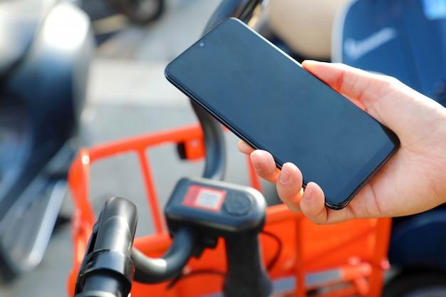 Gedeelde fietsen. hand met behulp van smartphone de qr-code van een gedeelde fiets in de stad scannen.