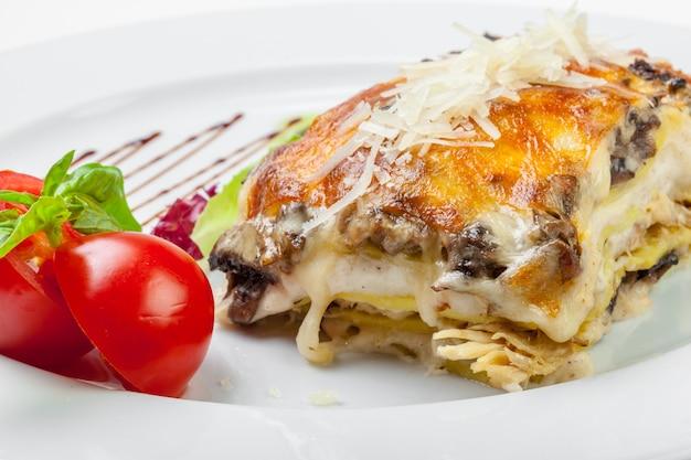 Gedeelte smakelijke lasagna, dat op wit wordt geïsoleerd