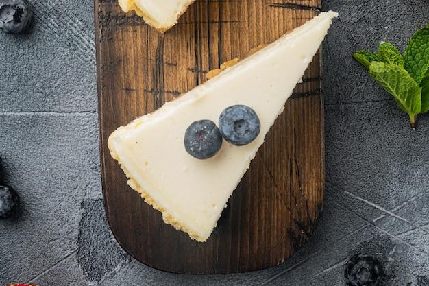 Gedeelte van cheesecake met bessen, op grijze achtergrond, bovenaanzicht plat lag