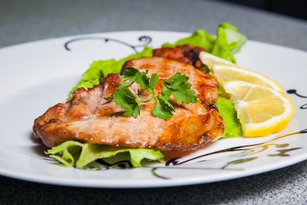 Gedeelte van gegrild vlees met citroen op plaat