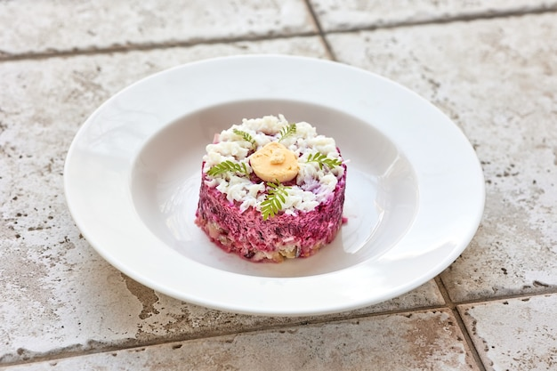 Gedeelte van haring en bietensalade op witte plaat