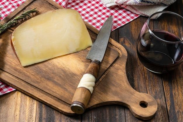 Gedeelte van landkaas op een houten snijplank met een glas rode wijn en een mes. landelijk tafereel.
